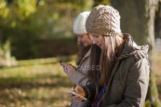 Studenti di sesso femminile che utilizzano smart phone all'aperto — Foto stock