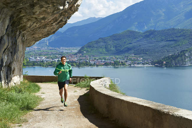 Hombre corriendo en el lago de Garda - foto de stock