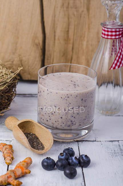 Bicchiere di frullato di mirtillo, fresca curcuma, pala di legno di semi di chia e mirtilli su legno — Foto stock