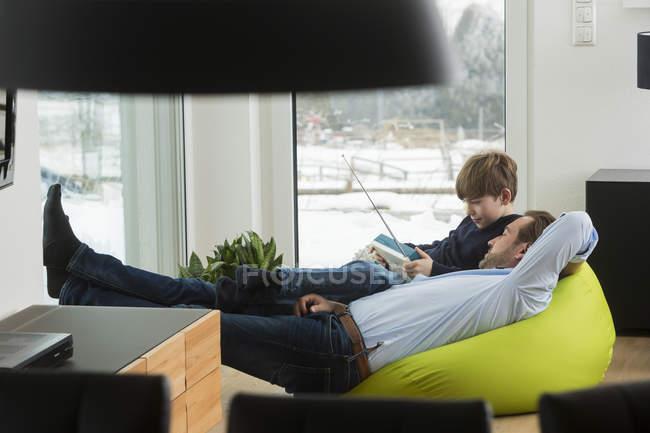 Отец и сын слушают старое радио в гостиной — стоковое фото