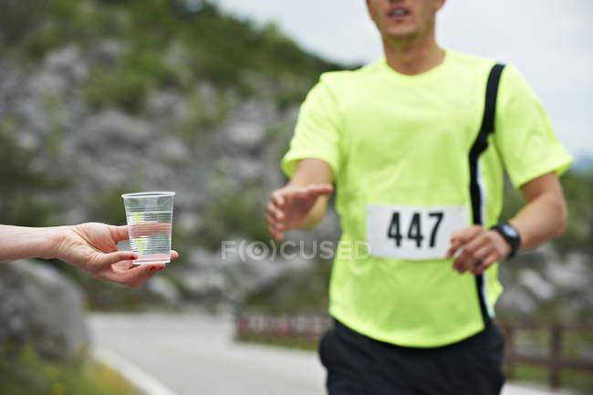 Homme recevant de l'eau à la compétition courante — Photo de stock