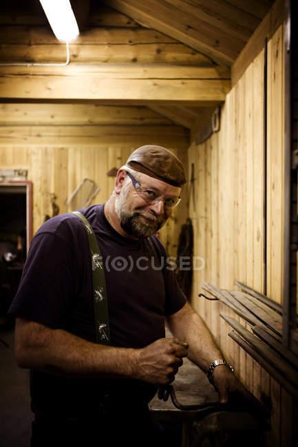 Портрет улыбающегося мастера в мастерской, смотрящего в камеру — стоковое фото