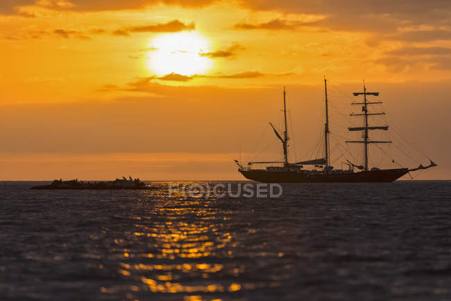 Pacific Ocean, sailing ship at Galapagos Islands at sunset — Stock Photo