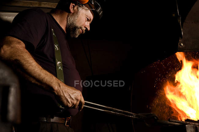 Blacksmith at work at the fireplace side view — Stock Photo