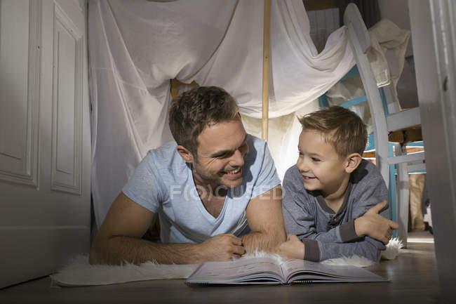 Vater und Sohn haben Spaß im selbstgebauten Zelt zu Hause — Stockfoto
