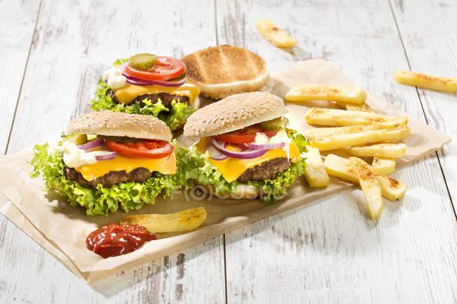 Hamburguesas de queso caseras con papas fritas en el escritorio de cortar sobre la superficie de madera - foto de stock