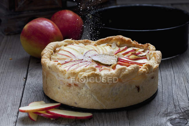 Sprinkling apple pie with icing sugar — Stock Photo