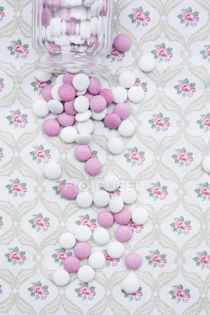 Pink and white chocolate buttons on floral patterned cloth — Stock Photo