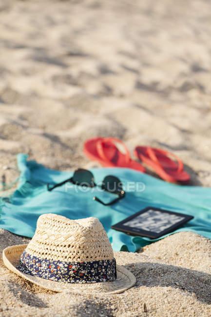 Полотенце, солнцезащитные очки, шлепанцы, соломенная шляпа и цифровой планшет на песчаном пляже — стоковое фото