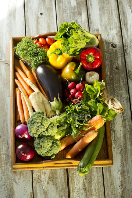 Wooden tray with different vegetables, top view — Stock Photo