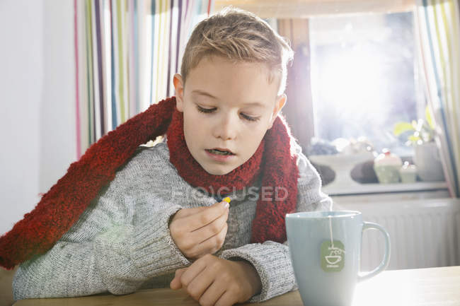 Boy sitting in the kitchen looking at tablet — Stock Photo