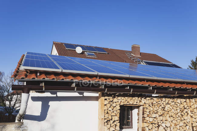Germany, solar panels on roof and storing of firewood under porch of a house — Stock Photo