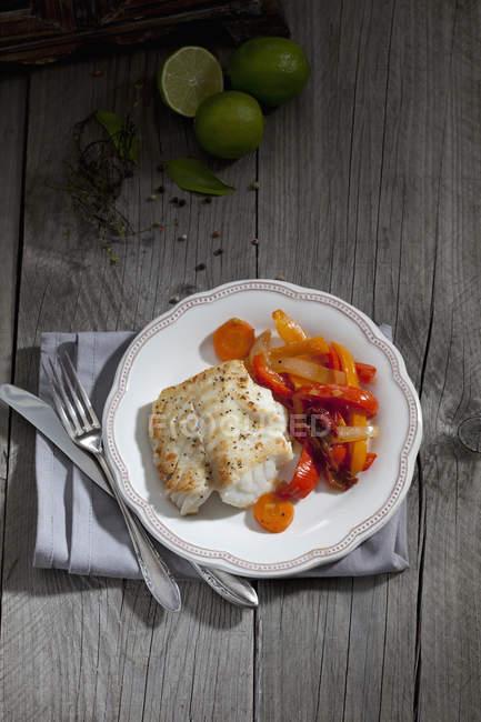 Жареная треска и овощи на плите с столовые приборы на деревянные поверхности — стоковое фото
