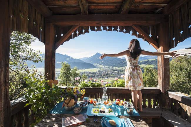 Austria, Stato di Salisburgo, Altenmarkt-Zauchense, donna che gode della vista dalla veranda del vecchio casale — Foto stock