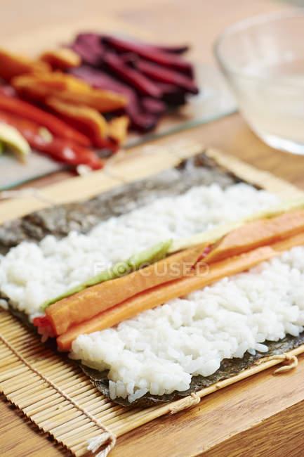 Detailansicht des Nori-Blatt bedeckt mit Sushi-Reis und Gemüse Füllung — Stockfoto