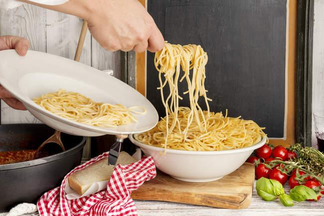 Donna, riempiendo gli spaghetti sul piatto, Spaghetti alla Bolognese — Foto stock