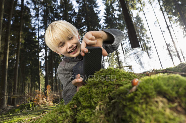 Germany, smiling little boy photographing nature in a forest — Stock Photo