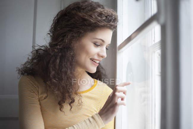 Улыбающаяся молодая женщина рисует сердце на стекле — стоковое фото