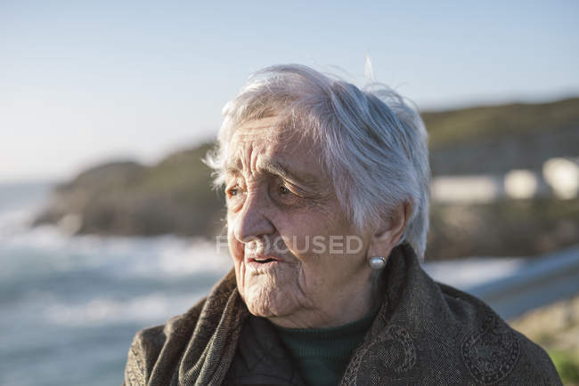 Portrait of old woman looking away at coast — Stock Photo