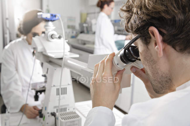 Scientists working in laboratory with microscope — Stock Photo