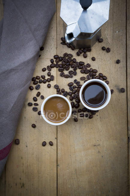 Two cups of coffee, cloth, espresso can and coffee beans — Stock Photo