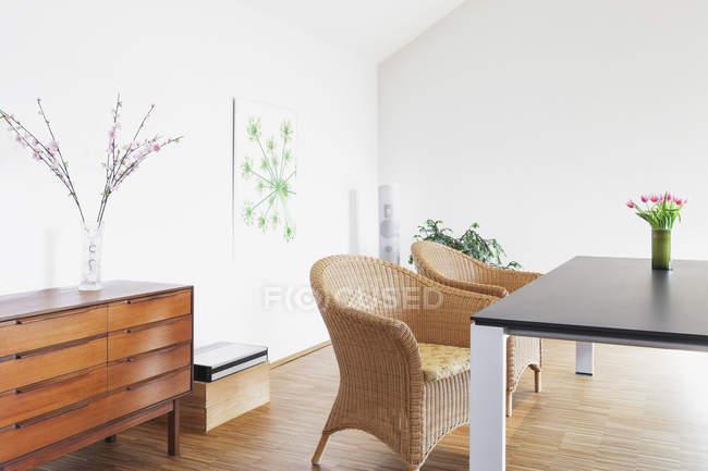 Comedor con pintura y flores en un ático - foto de stock