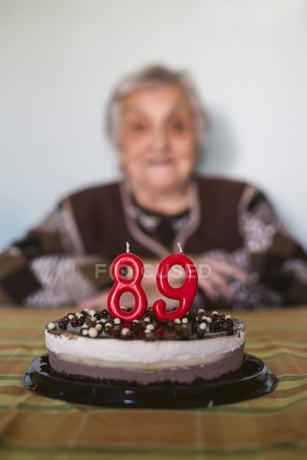 Vecchia donna festeggia 89esimo compleanno con torta festiva in primo piano — Foto stock