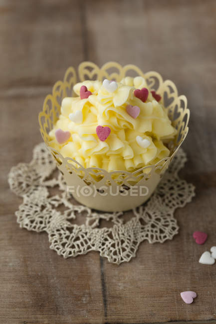Cupcake with buttercream decorated with sugar hearts on doily — Stock Photo