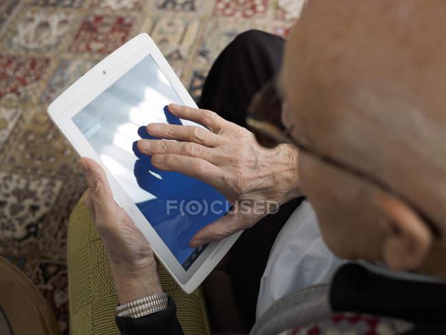 Vieil homme à la maison en utilisant une tablette numérique — Photo de stock