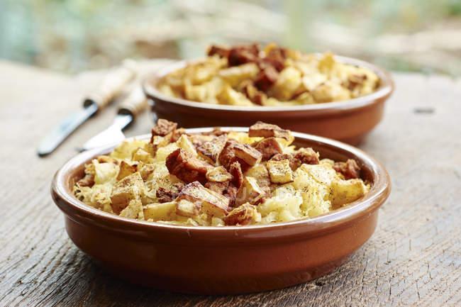 Chucrut, puré de cazuela de patatas con crujiente apio de raíz y tofu picante - foto de stock