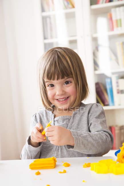 Портрет счастливой маленькой девочки, играющей с желтой модельной глиной — стоковое фото
