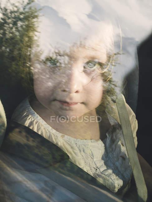 Kleines Mädchen sitzt im Auto und schaut aus dem Fenster — Stockfoto