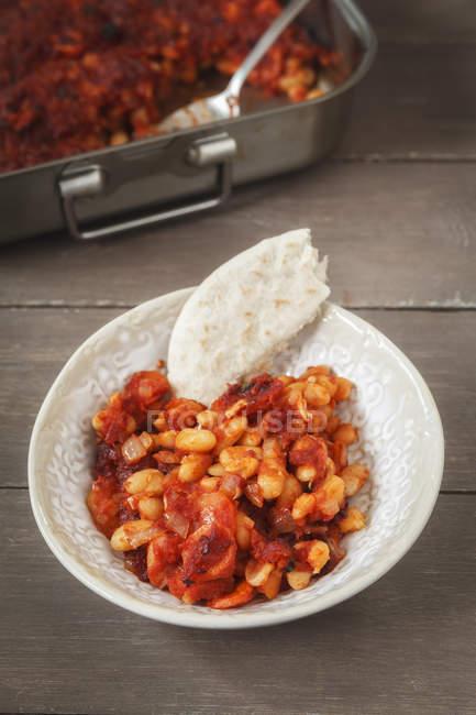 Vista elevada del plato con habas cocidas al horno, salsa de tomate y pan en mesa de madera - foto de stock