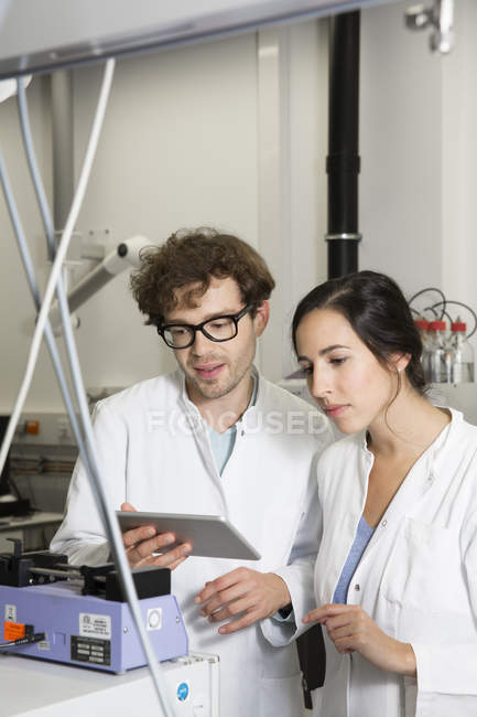 Scientists working with tablet computer in analytical laboratory — Stock Photo
