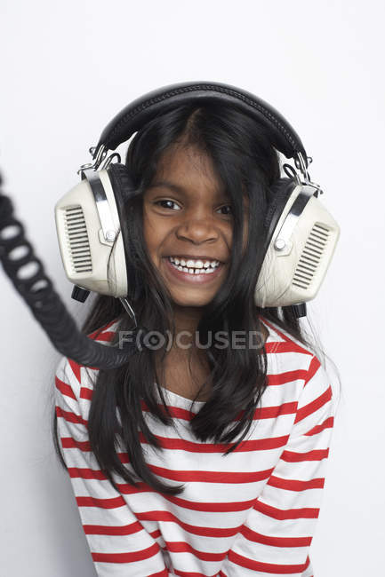 Portrait of smiling girl hearing music with headphones — Stock Photo