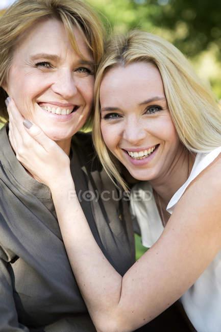 Retrato de mãe feliz e filha adulta no parque — Fotografia de Stock