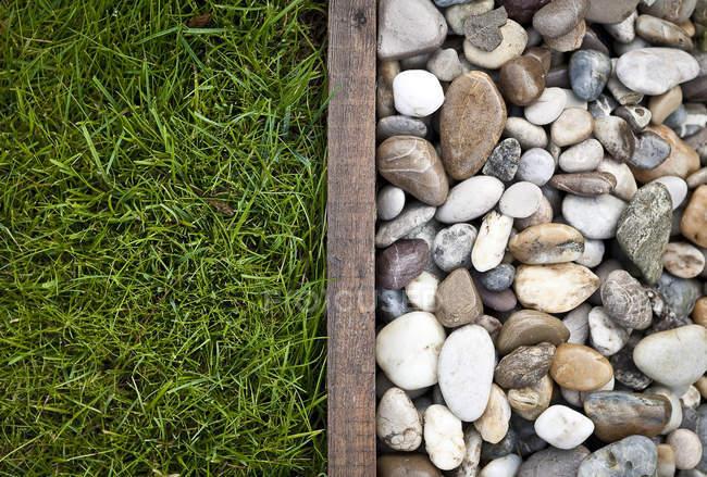 Gras getrennt von Kieselsteinen in einem Garten — Stockfoto