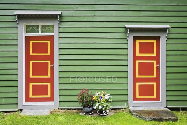 Noruega, fachada de la casa verde de madera, puertas de entrada sobre hierba - foto de stock