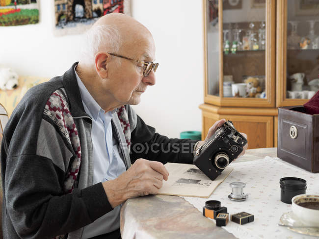 Senior man sitting at table and dealing with old camera — Stock Photo