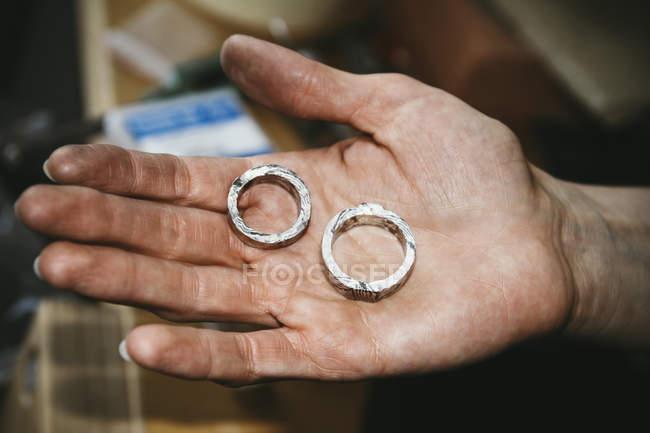 Goldschmied arbeitet an Trauringen im Mokume-Gane-Stil, Hand hält unfertigen Ring — Stockfoto