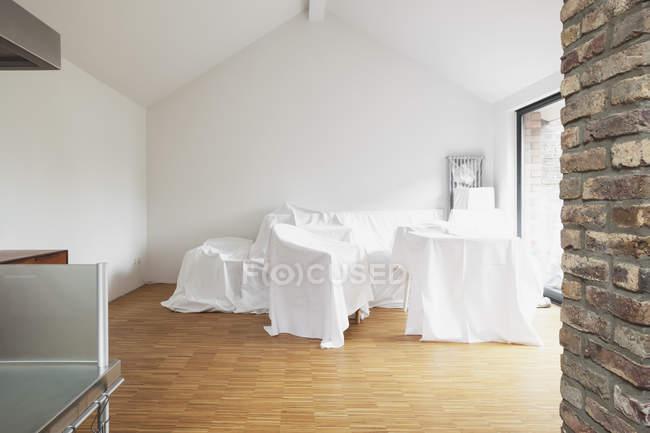 Vista di giorno di mobili rivestiti in tessuto bianco in attico — Foto stock