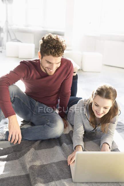 Lächelndes junges Paar mit Laptop auf dem Boden — Stockfoto