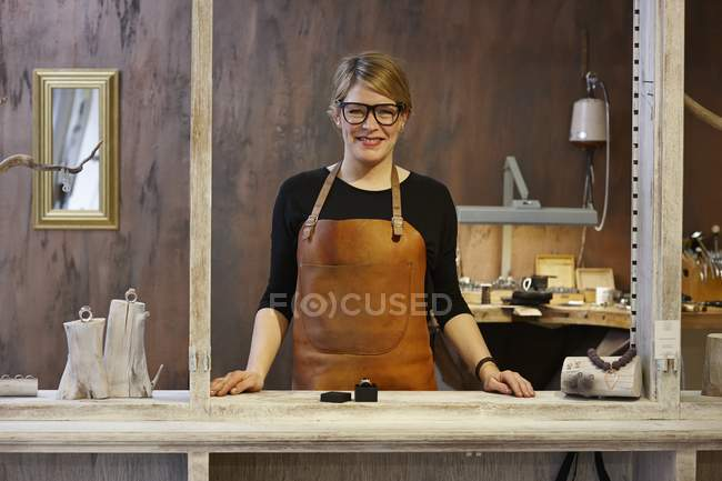 Portrait of smiling goldsmith in her shop — Stock Photo