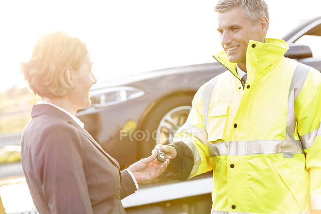 Businesswoman having an accident handing over car key to breakdown service man — Stock Photo