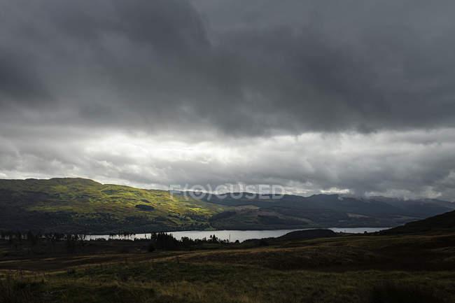 UK, Scotland, Scottish Highlands, dramatic sky over grass on hills — Stock Photo