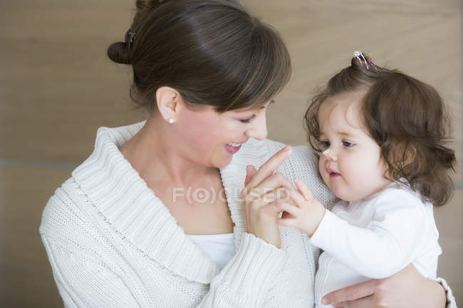 Woman applying creme on daughter's nose — Stock Photo