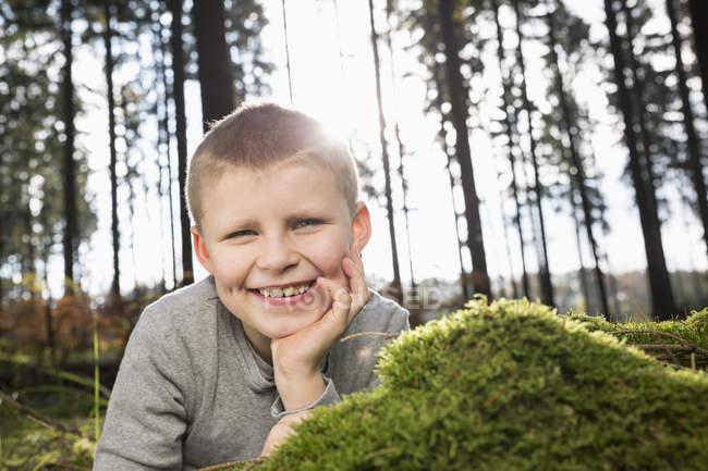 Portrait d'un petit garçon souriant dans une forêt — Photo de stock