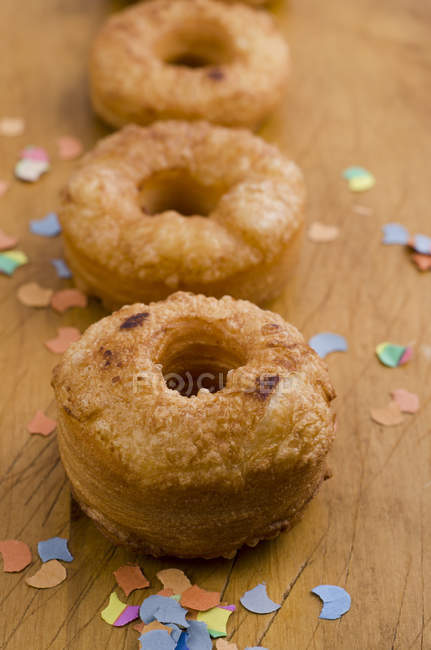 Close-up of Cronuts and confetti on wooden table — Stock Photo