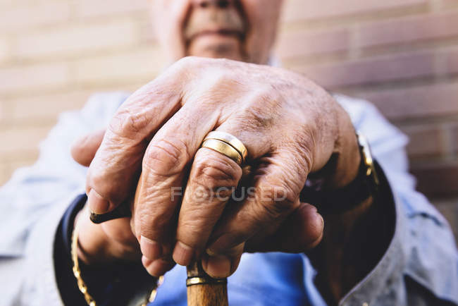 Close-up of old male hands resting on walking stick — Stock Photo