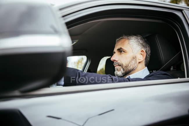 Portrait d'un homme au volant de voiture, regardant de côté — Photo de stock
